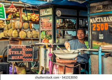 BALI - AUGUST 25: Local ambulant street vendor transporting her products on August 25, 2015 in Bali, Indonesia. Local vendors make an honest living selling snacks