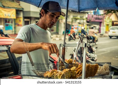 BALI - AUGUST 26: Local ambulant street vendor selling his products on August 26, 2015 in Bali, Indonesia. Local vendors make an honest living selling snacks