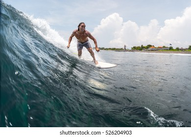 BALI, CANGGU - NOVEMBER 30 2016 Surfer riding on the wave in the ocean