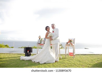 BALI FEBRUARY 2011 - Marriage couple is posing on the green grass in beautiful resort during outdoor wedding ceremonial
