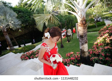 BALI FEBRUARY 2014 - Beautiful bridesmaid holding a white and red rose bouquet flower while walking to the chapel in before the wedding ceremony