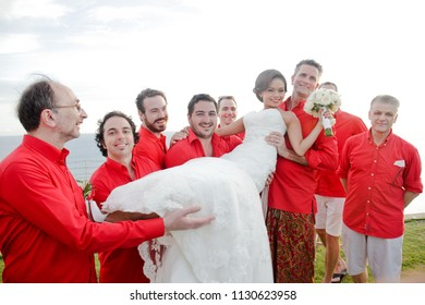 BALI FEBRUARY 2014 - Groomsmen are holding the bride right after the blessing ceremony in a cliff front resort during beautiful day in Bali