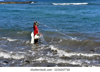 BALI - INDONESIA / 06.07.2018: Man fishing from beach in Candidasa, East of Bali Island, Indonesia