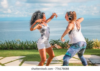 Bali, Indonesia - 10/09/2017: Two Women in a Dance Battle Overlooking the Blue Ocean at a Silent Disco Festival
