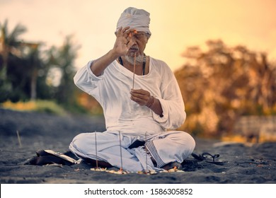 Bali, Indonesia - 12 Dec 2019: Old local balinese man in meditation near the sea. Concept of pray. Adult practice yoga on the Keramas black sand beach at sunset. Rural asian man doing yoga exercise.