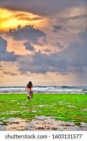 Bali, Indonesia 12/31/2019: Rear view of teenage asian girl walking on beach, Bali, Indonesia