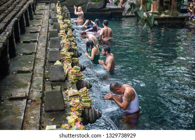 Bali, Indonesia : 14 July 2018 : Group of tourist and Balinese people taking a bath in Pura Tirta Empul the holy spring water temple in Bali, Indonesia.