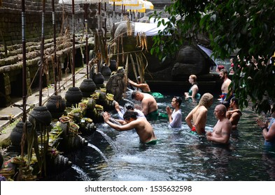 Bali, Indonesia- 18 Oct, 2019: Indonesian and tourism pray and bath themselves in the sacred waters of the fountains, in Tirta Empul, Bali, Indonesia