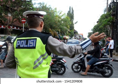Bali, Indonesia- 18 Oct, 2019: Road policeman controls the traffic of vehicles in Bali, Indonesia.