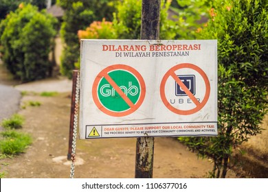 BALI, INDONESIA - 21 May, 2018: A protest sign on a wall in Indonesian objecting to Uber and Grab taxi drivers reads 'Uber and Grab Taxis No Entry' in Ubud, Bali, Indonesia.