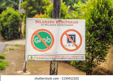 BALI, INDONESIA - 21 May, 2018: A protest sign on a wall in Indonesian objecting to Uber and Grab taxi drivers reads 'Uber and Grab Taxis No Entry' in Ubud, Bali, Indonesia