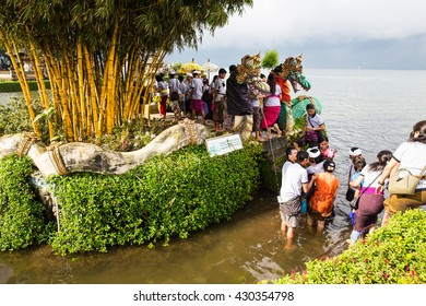 Bali Indonesia - 5 May 2016: Getting wet to cross to another side, for a ceremony on the small holy island at Pura Ulun Danu Bratan (Temple of water)