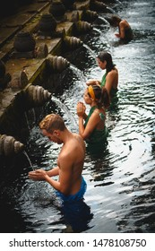 BALI, INDONESIA - 8 AUGUST 2019: People at the holy spring water is praying at Pura Tirta Empul temple during a religious ceremony in Tampa, Bali, Indonesia.
