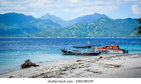Bali, Indonesia - Apr 17, 2016. Tourist boats waiting on sand beach at summer day in Bali Island, Indonesia.