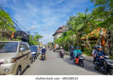 BALI, INDONESIA - APRIL 05, 2017: Motorcyclist going down the road in ubud, Bali