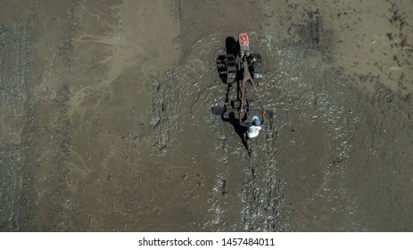Bali, Indonesia - April 18, 2019: Traditional way of rice field plowing in Bali, Indonesia. Man working with old mechanical hand plow, field in mud. Drone view from above.