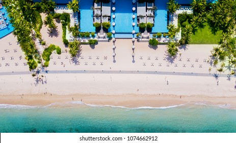 BALI, INDONESIA. APRIL 19, 2018: Top view of swimming pool near coastline at Nusa Dua Beach in Bali, Indonesia