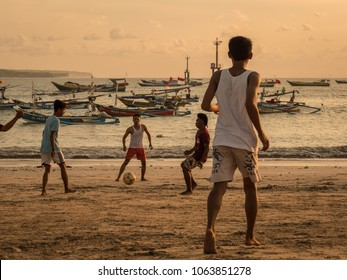 Bali, Indonesia - April 2, 2018: Young fotball players playing fotball on the beach at sunset. Fishing boats on the background. Active lifestyle in southeast asia.