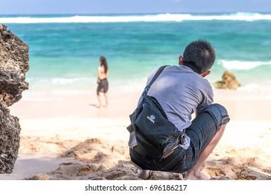 BALI, INDONESIA - AUGUST 12, 2017: Asian photographer on a secret beach of Bali island.