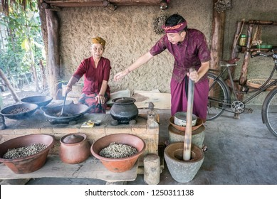 Bali, Indonesia - August 13th 2018: Old woman and young man roasting luwak coffee beans in Ubud. Luwak coffee is very expensive and famous Balinese cofee