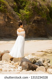 Bali, Indonesia - August 21, 2018: Silhouette of lonely young woman in white wedding dress looking into the distance at the beach. Dreaminess. Romantic style. Theme of loneliness.