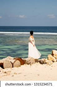 Bali, Indonesia - August 21, 2018: Lonely young woman in white wedding dress looking into the distance standing on the barrels at the beach. Ocean view background. Thoughtfulness. Romantic style.