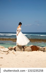 Bali, Indonesia - August 21, 2018: Lonely young woman in wedding dress standing on the barrels at the beach. Ocean view background. Thoughtfulness. Romantic style.