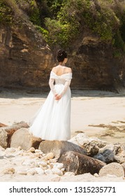 Bali, Indonesia - August 21, 2018: Rear view of lonely young woman in white wedding dress looking into the distance standing on the vintage barrels at the beach. Dreaminess. Romantic style.