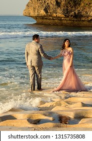 Bali, Indonesia - August 21, 2018: Young happy couple in love holding each other hands standing on the Balangan beach. Exotic Balinese ocean shore. Tenderness and love. Romantic style.