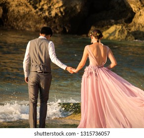 Bali, Indonesia - August 21, 2018: Rear view of young happy couple in wedding outfits holding each other hands on the Balangan beach. Exotic Balinese ocean shore. Tenderness and love. Romantic style.