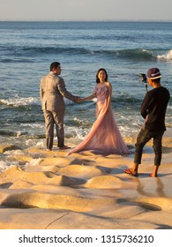 Bali, Indonesia - August 21, 2018: Young happy couple, photographer assistant on the Balangan beach. Love story photoshoot in progress. Exotic Balinese ocean shore. Tenderness and love. Romantic style