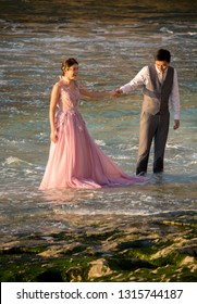 Bali, Indonesia - August 21, 2018: Happy young couple in wedding outfits holding each other hands standing in the water of Balangan beach. Exotic Balinese ocean shore. Tenderness and love. Romance.