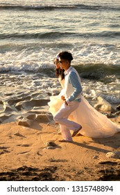 Bali, Indonesia - August 21, 2018: Happy couple in stylish wedding outfits running on the beach. Love story concept. Modern Balinese wedding ceremony. Enjoy of life. Stunning sunset ocean view.
