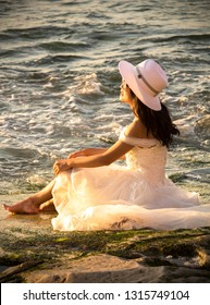 Bali, Indonesia - August 21, 2018: Close-up young woman in stylish wedding outfit sitting on the Balangan beach shore. Stunning ocean view background. Romantic style. Happiness. Enjoy of life.