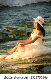 Bali, Indonesia - August 21, 2018: Close-up young woman in white wedding outfit sitting on the Balangan beach shore. Stylish look the modern wedding dress with hat. Stunning ocean view. Romantic style