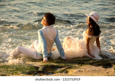 Bali, Indonesia - August 21, 2018: Happy couple in stylish white wedding outfits sitting on the beach. Love story concept. Modern Balinese wedding ceremony. Enjoy of life. Stunning sunset ocean view.