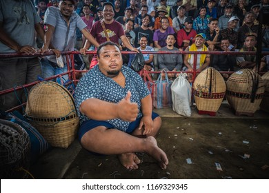 BALI, INDONESIA - AUGUST 25, 2018: The assistant during a cockfight, two fighting hens, which is ancient balinese tradition to fight evil spirits