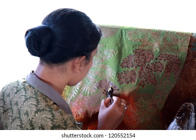 BALI, INDONESIA - AUGUST 26, 2011: An unidentified Balinese woman applies dye on a piece of batik, on August 26, 2011 in Bali, Indonesia. Batik-making is an important part of Indonesian culture.
