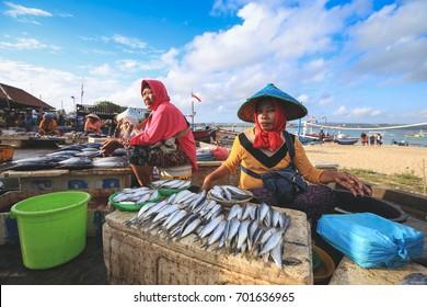 BALI, INDONESIA - AUGUST 8, 2017 : Balinese fishmonger sells fish in the morning market in Kedonganan - Passer Ikan, Jimbaran beach