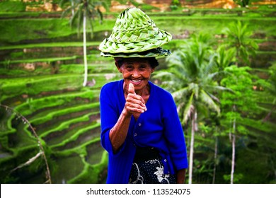 BALI, INDONESIA - CIRCA AUGUST 2011:woman sells hats near a rice terrace circa August 2011 in Bali. Balinese people always look happy no matter how hard they work and little they earn for living.