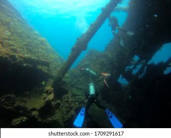 Bali, Indonesia - Circa February 2020: Divers swimming through Tulamben Wreck in Bali, Indonesia