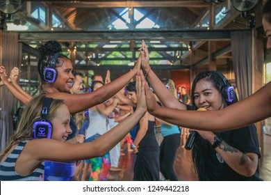 Bali, Indonesia - December 1, 2018: Girls High Fiving with Smiles on their Faces during a Silent Disco Dance Party