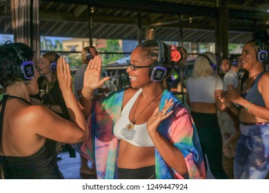 Bali, Indonesia - December 1, 2018: Two Girls about to High Five with Headphones on during Silent Disco Dance