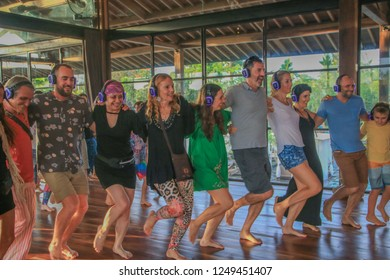 Bali, Indonesia - December 1, 2018: Group of Dancing People in a Kick Line during Silent Disco Party