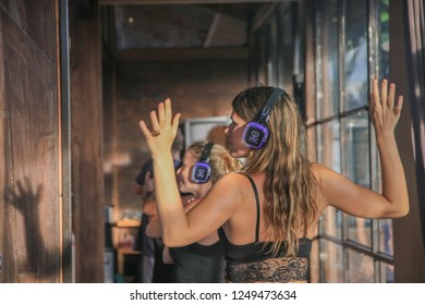 Bali, Indonesia - December 1, 2018: Young Caucasian Woman with her Arms Spread Dancing at Silent Disco Party