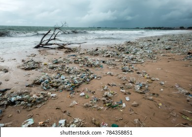 Bali, Indonesia - December 19, 2017: Garbage on beach, environmental pollution in Bali Indonesia. Storm is coming on background. And drops of water are on camera lens. Dramatic view