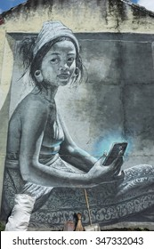 BALI, INDONESIA - December 5, 2015: Street graffiti of a young, topless Balinese woman from an earlier era using a smartphone on December 5, 2015 in Ubud, Bali, Indonesia.