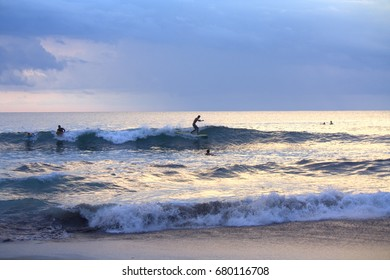 Bali, Indonesia - February 20, 2016 : Surfing enthusiast at Canggu beach. Bali is an ideal place to learn how to surf, ride the waves, regardless of your skill level. Image contain noise.