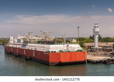 Bali, Indonesia - February 25, 2019: Red and white Floating Storage and Regasification Unit, FSRU, LNG-vessel in Benoa Harbour under light blue sky.