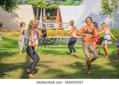 Bali, Indonesia - February 3, 2018:  Women Dancing Outdoors with Headphones on Grass